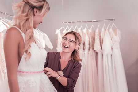 Cheerful nice woman looking at her client while working on her dress