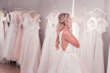 Positive young woman looking at the wedding dresses while being in the wedding boutique