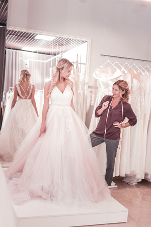 Nice female tailor holding her glasses while looking at the bride