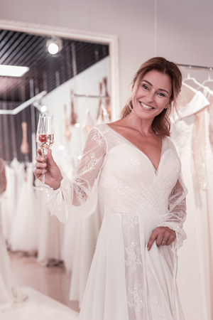 Happy delighted bride holding a glass with champagne while celebrating her future wedding