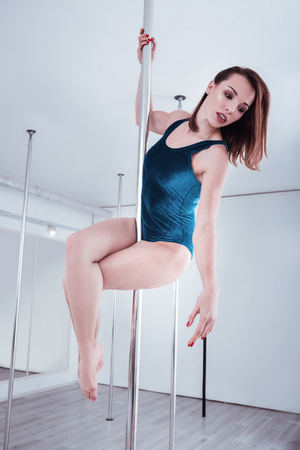 Beautiful young pole dancer feeling truly joyful and cheerful while dancing good Stok Fotoğraf