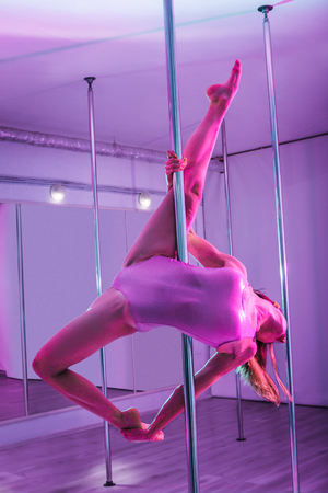 Beautiful slim pole dancer making amazing performance for her students in light studio