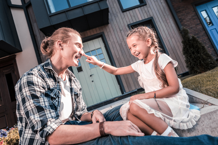 Loving blonde-haired father entertaining his cute little beautiful girl wearing white dress