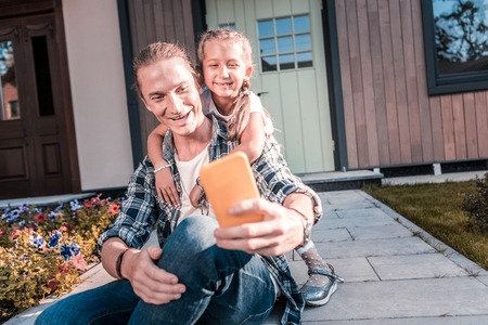 Blonde-haired handsome father holding yellow smartphone making selfie with daughter Фото со стока