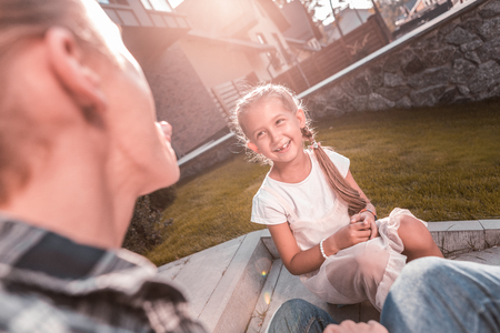 Cute dark-eyed beaming girl feeling extremely cheerful and funny talking with father