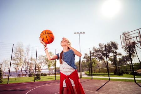 Amazing girl keeping smile on her face while playing basketball alone Stock Photo