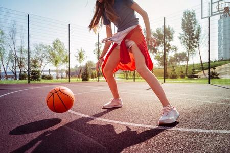 Activity on nature. Joyful teenager being on stadium while playing basketball Stock Photo