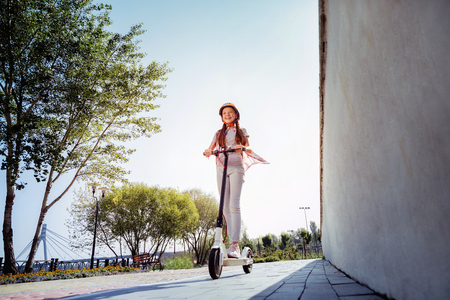 Cheerful girl keeping smile on her face while standing on push-cycle
