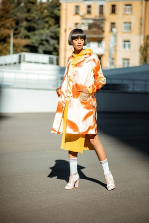 Brunette stylish woman with bob hairstyle wearing bright orange coat while posing on parking area