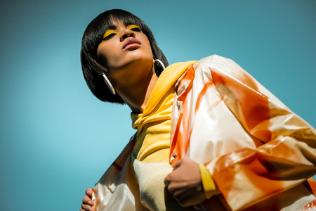 Unusual short-haired woman wearing bright orange poncho and staying against blue sky