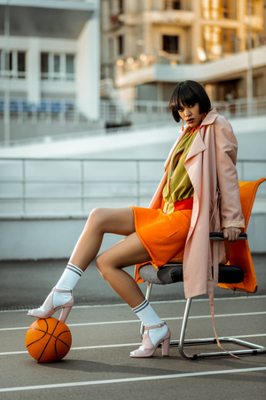Drastic woman sexually posing with orange ball wearing layered bright outfit