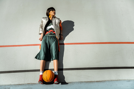 Adorable skinny girl staying against the wall with ball between her legs in warm outfit