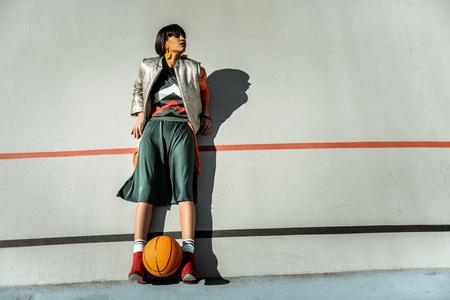 Entzückendes dünnes Mädchen, das mit Ball zwischen den Beinen in warmem Outfit an der Wand bleibt