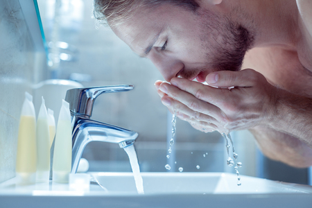 Bearded handsome blonde-haired man washing his face in the morning in light bathroom