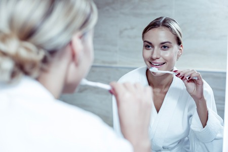 Beautiful blonde-haired woman wearing white bathrobe brushing her teeth in the morning