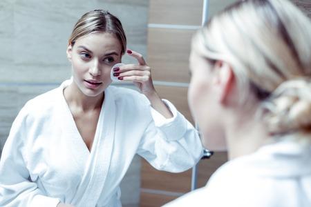 Strahlende blonde Frau mit weißem Bademantel, die ihre Haut vor dem Schlafen säubert Standard-Bild