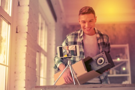 Joyful handsome blogger showing item from cardboard box to his audience in the Internet
