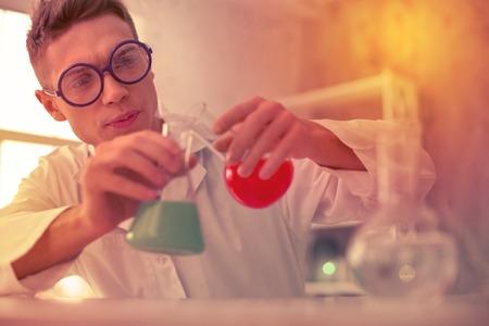 Unconfident handsome teacher blending reagents in glass tubes for chemistry experiment Stock Photo
