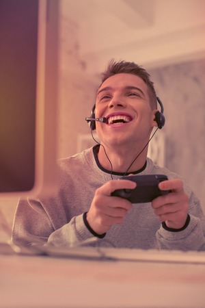 Short haired gamer openly smiling while playing exiting computer game at home