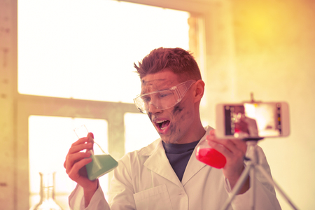 Confused failed chemist with dirty face due to reaction of mixed reagents 免版税图像