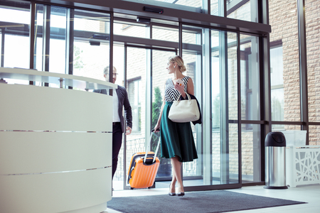 Couple of prosperous businessmen with luggage entering hotel while coming on business trip