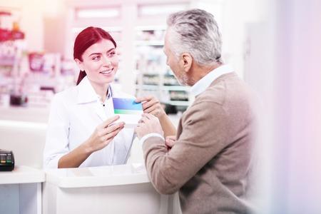 Encantador boticario de pelo oscuro que presenta una caja azul con pastillas a un comprador mayor interesado en una farmacia Foto de archivo