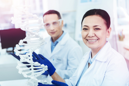 Joyful positive woman standing near the DNA model while studying it