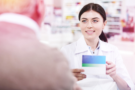 Smiling dark-haired pharmacist in white uniform presenting a white and blue box of medication to a client of the drugstore