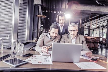 Watching video. Cheerful mature man wearing glasses while working at computer Standard-Bild