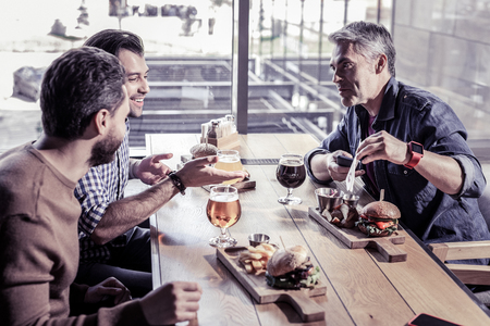 Cheering up the friend. Cheerful young males sitting at the table while enjoying friendly atmosphere 版權商用圖片 - 113235708