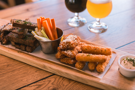 So yummy. Close up of wooden plate that being on table, fast food lying near beer