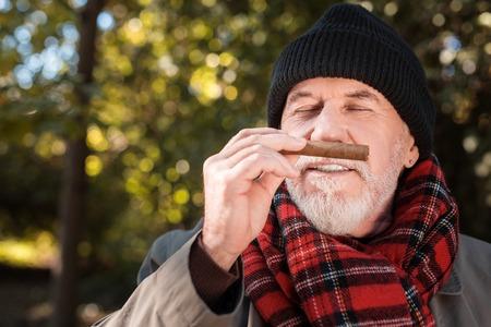 Joyful nice man putting cigar to his nose while enjoying its smell