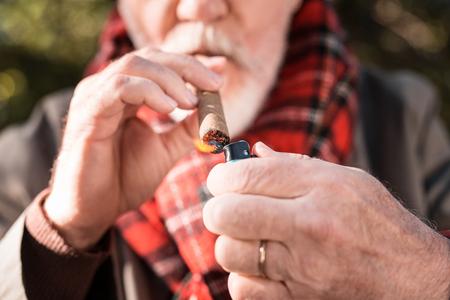 Real cigar. Selective focus of a Cuban cigar being lit by a nice pleasant man Reklamní fotografie