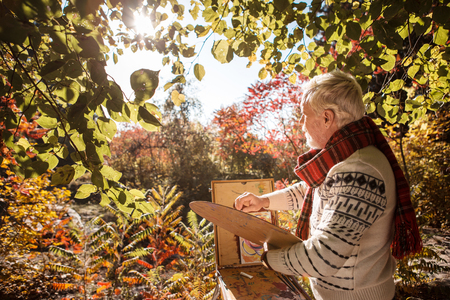 Power of inspiration. Joyful talented artist looking at the autumn trees while painting them