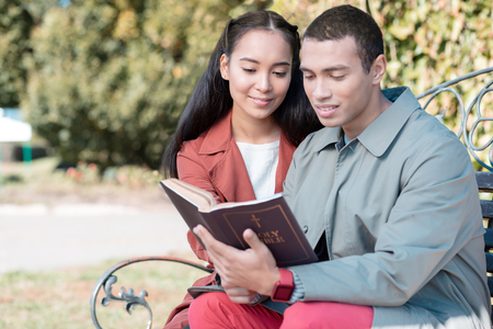 Reading about fate. Handsome brunette man keeping smile on his face while reading Holy Bible