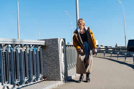 Walk the bridge. Beautiful dark-haired young woman wearing oversize coat walking the bridge