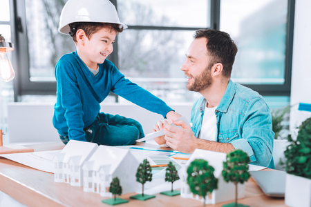 Great family. Joyful positive child helping to his father while being in an office