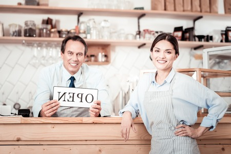 Professional service. Joyful beautiful woman smiling to you while standing at the counter Reklamní fotografie