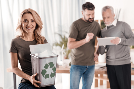 Preserving environment. Alert blond woman smiling and holding a litter bin