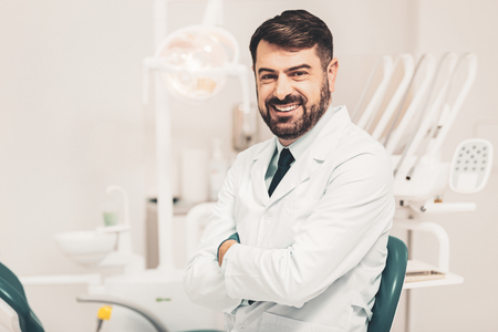 Dentist at workplace. Cheerful bearded doctor sitting in spacious modern office and looking at camera with smiling kind heartedly and keeping his hands in crossed position