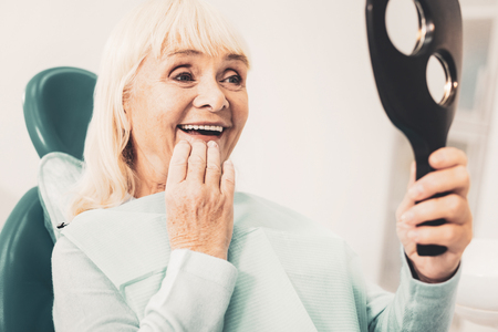 White smile. Close up of mature smiling woman holding mirror and viewing her new denture while touching her chin with hand Stock fotó