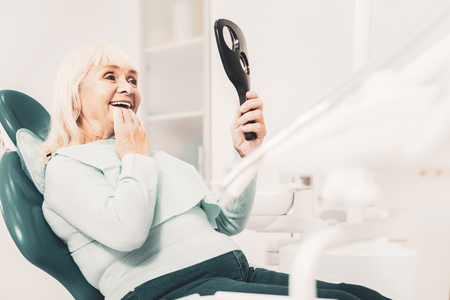 Cheerful old lady sitting in dental chair with smile while viewing her new teeth in the mirror and feeling pleased Stock fotó - 113277664