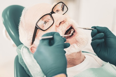 Teeth examination. Close up of senior patient opening his mouth while skilled doctor holding dental instruments and checking patients mouth cavity