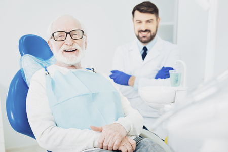 Great doctor. Cheerful senior man sitting in dentist chair while laughing