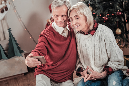 Amazing female person keeping smile on her face and holding hands together while looking at camera Stock Photo