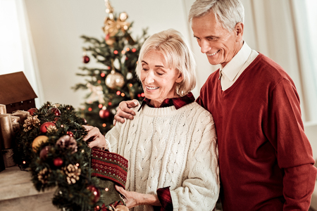 Ready for holiday. Pleasant lovely elderly couple standing in the bright room smiling and overlooking decorations.