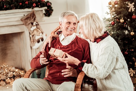 Unexpected gift. Surprised happy aged man sitting on the chair near his wife smiling and taking a present.