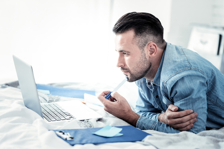 Handsome bearded man lying on elbows and touching chin with pen while working at his project