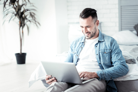 Good news. Attractive male person keeping smile on his face and holding computer on knees while checking his mailbox Stock Photo