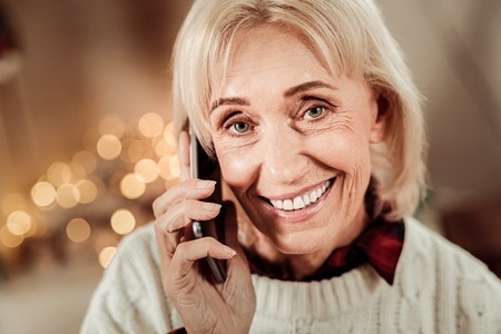 Best connection. Pleasant elderly occupied woman being in the bright room smiling and having conversation. Imagens